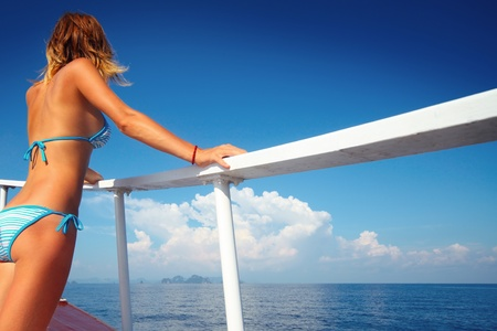 recreation yachts: Young woman standing on a ships board and looking to a horizon
