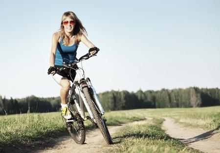 andando en bicicleta: Mujer joven montado en una bicicleta en un camino rural