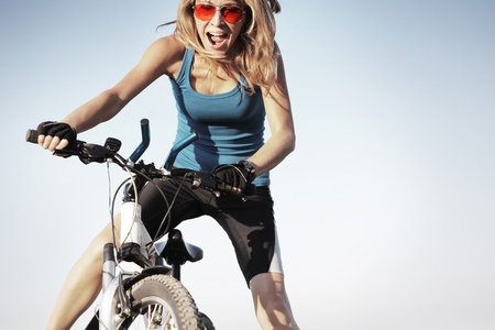 dynamic activity: Young woman holding handlebar of a bicycle and shouting