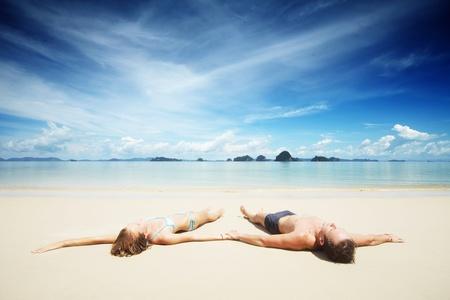 Pareja joven tumbado en la arena blanca de un centro turístico