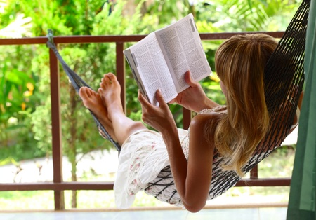 Young woman lying in a hammock in garden and reading a book photo