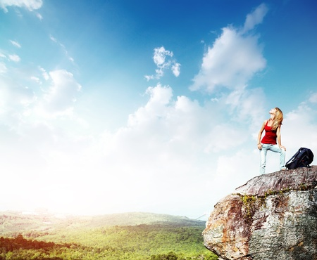 Young woman with backpack standing on a cliffs edge and looking to a sky photo