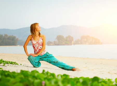 Young woman doing yoga exercises on a beach photo