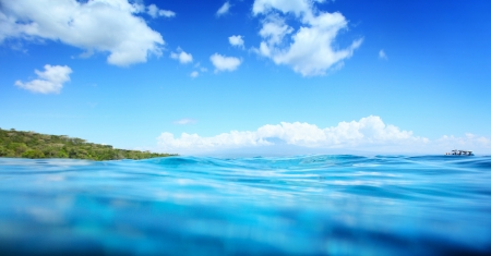 Blue clear tropical sea and green island on the horizon Stock Photo - 16834655