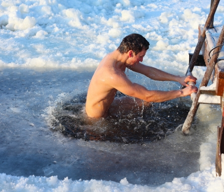 sunny cold days: Young man swimming in an ice hole Stock Photo