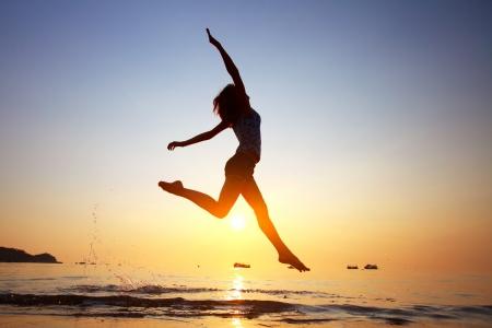 manos levantadas al cielo: Mujer joven que salta en un agua en una playa Foto de archivo