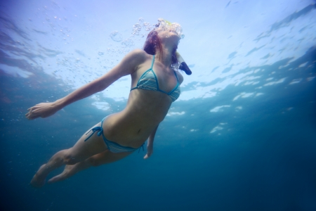 under the surface: Young woman freediving in a clear sea