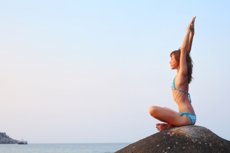 Young woman stretching on a rock at sunset light photo