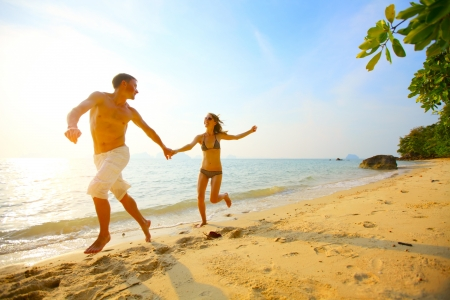 Young couple running on a tropical beach at sunset photo