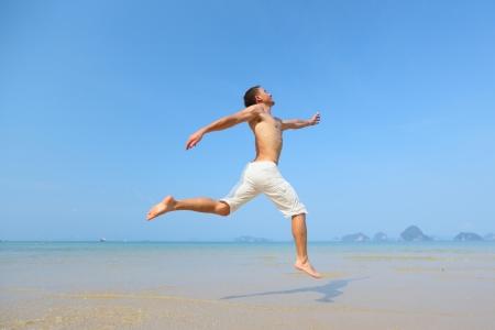 nacked: Semi nacked man jumping on a tropical beach