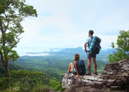 Young tourists with backpacks enjoying valley view from top of a mountain Stock Photo
