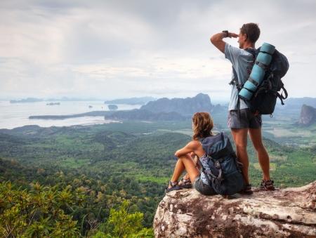 mujer mirando el horizonte: Turistas jóvenes con mochilas disfrutando vista del valle desde la cima de una montaña. Pseudo HDR Foto de archivo