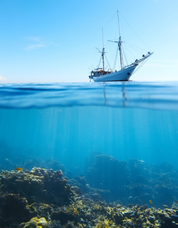 Sail boat in tropical calm sea and coral reef underwater photo