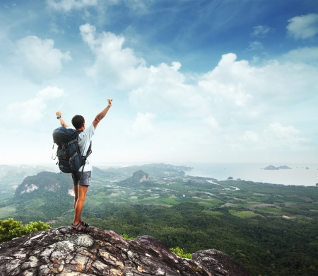 on the mountain: Young man with backpack standing with raised hands on top of a mountain and enjoying valley view