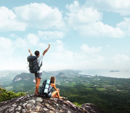 team journey: Two young backpackers enjoying a valley view from top of a mountain Stock Photo