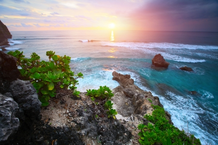 stormy sea: Rocky coast of Indian ocean at sunset light. Bali island Stock Photo