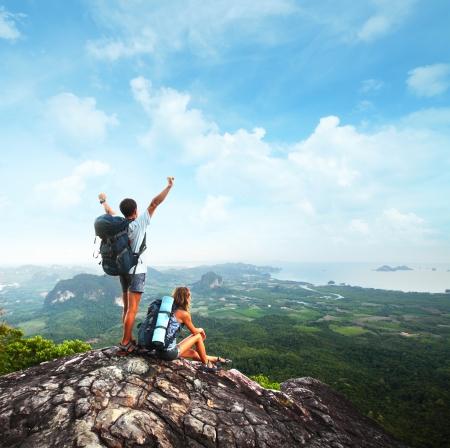 mászó: Fiatal turisták hátizsákok élvező völgy kilátás egy hegy tetején