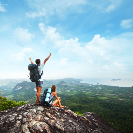 climbing: Turistas j�venes con mochilas disfrutar de vistas al valle desde la cima de una monta�a Foto de archivo