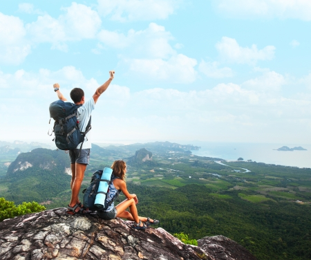Young tourists with backpacks enjoying valley view from top of a mountain photo