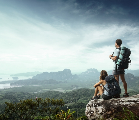 bergbeklimmen: Jonge backpackers genieten van een uitzicht op de vallei van de top van een berg
