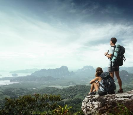 escalada: Mochileiros jovens desfrutando de uma vista do vale do alto de uma montanha
