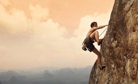 escalando: Hombre joven que sube en una pared de piedra caliza con amplio valle en el fondo