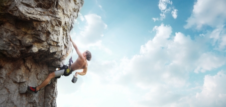 belay: Young man climbing vertical wall with belay with blue cloudy sky on the background