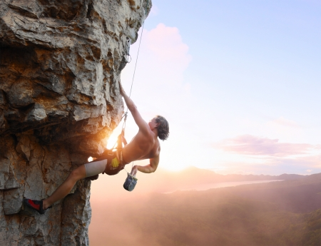 climbing sport: Young man climbing vertical wall with belay with sunrise valley on the background