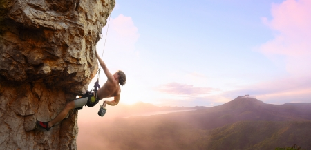 thrill: Young man climbing vertical wall with belay with sunrise valley on the background