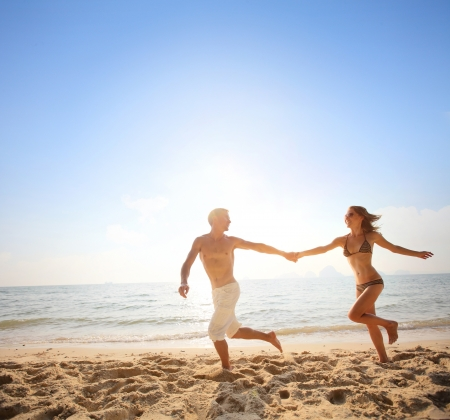 Young happy couple running together among a beach at sunny day photo