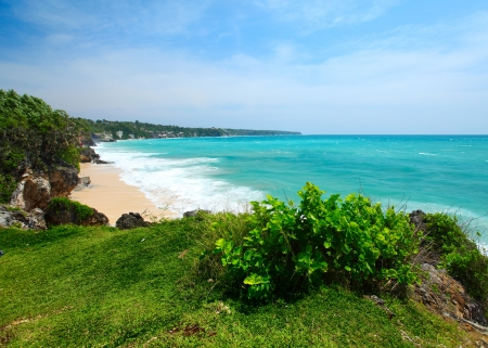 Green grass on meadow on a coast and blue ocean waves. Bali island photo