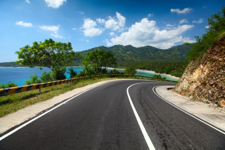 tropical border: Asphalt road along a tropical sea coastline Stock Photo