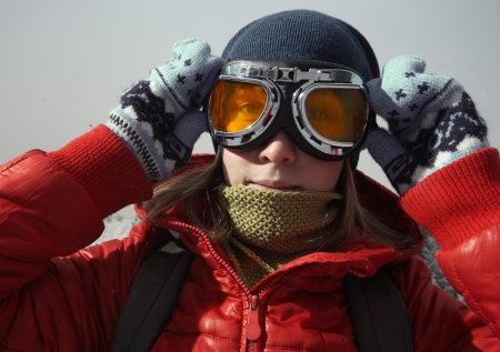 Young woman with goggles and backpack looking to a camera on a grey background Stock Photo - 16900106