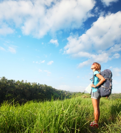 tourist guide: Young smiling woman standing on a green meadow with map and backpack and looking to a blue sky