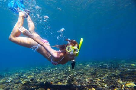 undersea: Young woman diving on a breath hold and making bubbles over coral reef in blue transparent sea