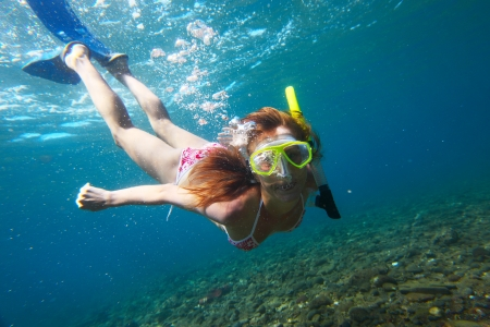 freediving: Young woman diving on a breath hold and making bubbles over coral reef in blue transparent sea