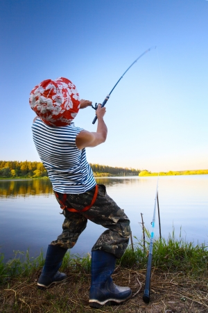 twitch: Fisherman standing on a coast of pond and pulling a fish Stock Photo