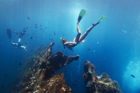 snorkeling: Young woman diving on a breath hold and finning in blue transparent sea near wreck USAT Liberty, Tulamben, Indonesia