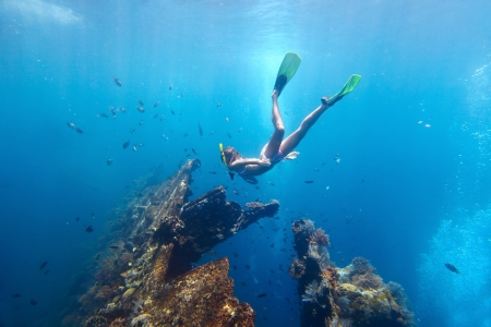 Young woman diving on a breath hold and finning in blue transparent sea near wreck USAT Liberty, Tulamben, Indonesia photo