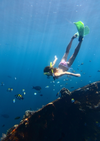 Young woman diving on a breath hold and finning in blue transparent sea near wreck Tulamben, Indonesia