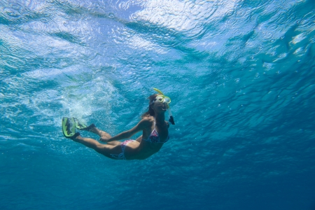 fining: Underwater shoot of a young woman in clear sea Stock Photo