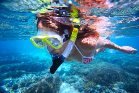 under water: Young woman snorkeling over coral reef in tropical sea with clear transparent water