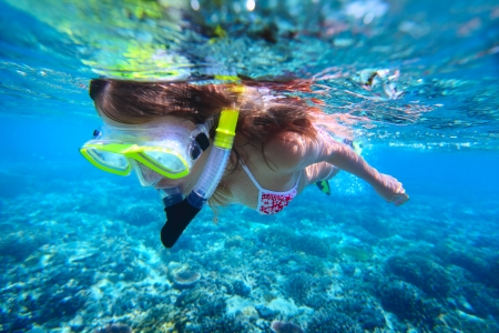 Young woman snorkeling over coral reef in tropical sea with clear transparent water