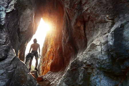Young explorer standing in a cave with climbing equipment ready for action photo
