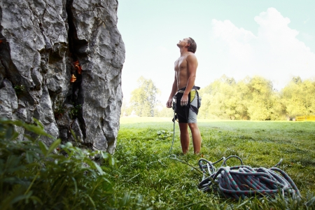 fearless: Young climber ready to conquer vertical wall with belay. Blue sky on the background Stock Photo