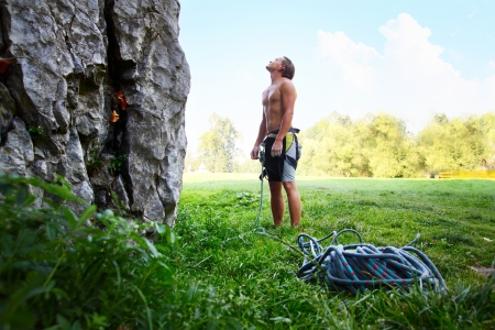 belay: Young climber ready to conquer vertical wall with belay. Blue sky on the background Stock Photo