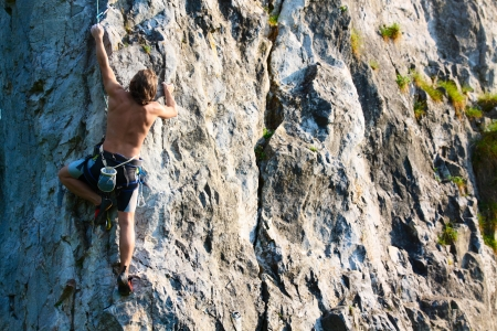 Young man climbing vertical wall with belay Stock Photo - 16835825