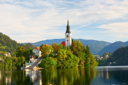 slovenia: Catholic church situated on an island on Bled lake with mountains and villages on the background Stock Photo