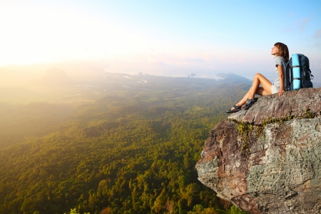 Young woman with backpack sitting on a cliff and enjoying a view Stock Photo