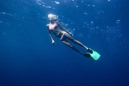 Young woman diving on a breath hold and finning in blue transparent sea photo